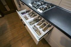 Roestvrij staallepels, vorken en knifes in de lade van de bestekdoos in witte keukenkast royalty-vrije stock foto's