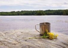 Roestvrij staalmok op steen dichtbij water op aardachtergrond Royalty-vrije Stock Foto