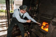 Roetige stoker die steenkool in de oven van de stoommotor scheppen stock fotografie