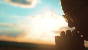 Rogación femenina joven hermosa la muchacha dobló sus manos en puesta del sol de la silueta del rezo vídeo de la cámara lenta La  metrajes
