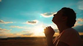 Rogación femenina joven hermosa la muchacha dobló sus manos en silueta del rezo en la puesta del sol vídeo de la cámara lenta La  metrajes