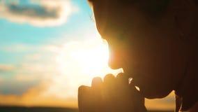 Rogación femenina joven hermosa la muchacha dobló sus manos en silueta del rezo en la puesta del sol vídeo de la cámara lenta La  almacen de video