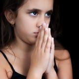 Rogación hispánica de la muchacha aislada en negro Imagenes de archivo