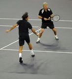 Roger Federer and Bjorn Borg in actions. Tennis players Roger Federer of Switzerland and Bjorn Borg of Sweden actions during an exhibition tennis match against royalty free stock photography