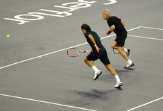 Roger Federer and Bjorn Borg in actions. Tennis players Roger Federer of Switzerland and Bjorn Borg of Sweden actions during an exhibition tennis match against Royalty Free Stock Image
