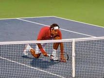Roger Federer est allé vers le bas sur un genou devant le filet de tennis Image stock