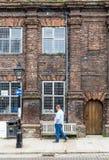 ROGGE, het UK/eerste van JUNI 2014 - een onbekende mens die voor een oud baksteenhuis lopen Royalty-vrije Stock Afbeeldingen