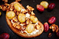 Roggetoost met gebakken witte druif, okkernoot en ricotta Stock Fotografie