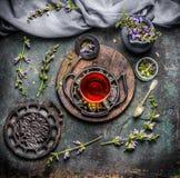 Rogivande kopp av örtte med nyast organiska ingredienser: örter och blommor på lantlig tappningbakgrund med tehjälpmedel arkivbild