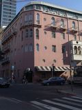Rogu ulicego widok rozdroże i różowy cztery opowieści budynek z parkującymi samochodami obraz stock