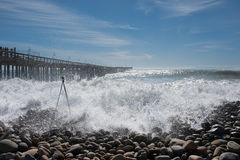 Rogue wave white water washing over camera tripod. Royalty Free Stock Photography
