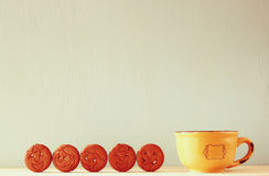 Roh von den Plätzchen mit smileygesicht über Holztisch nahe bei Tasse Kaffee Bild ist der gefilterte Retrostil Lizenzfreie Stockfotos