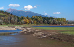 Rohace from Bobrovnik, Slovakia. Autumn view of shore with low water level at Liptovska Mara lake in foreground. Colorful trees and Rohace mountains can be seen stock photo