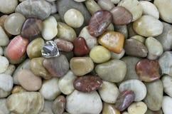 Rohdiamant; Natürlicher farbiger kleiner glatter Steinhintergrund Stockfotografie