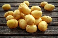 Rohe Babyfrühkartoffeln auf rustikalem hölzernem Hintergrund stockbild