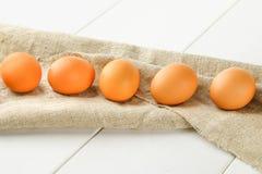 Rohe braune Hühnereien in einer Reihe auf Leinwand auf einem weißen Holztisch Bestandteile für das Kochen Stockbild