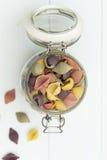 Rohe cocciolette Teigwaren auf einem Glasgefäß Stockbild