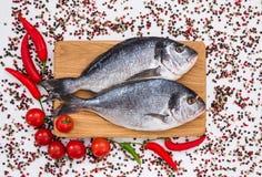 Rohe dorado Fische auf hölzernem Schneidebrett mit Gemüse Beschneidungspfad eingeschlossen Lizenzfreies Stockfoto