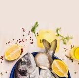 Rohe dorado Fische mit Öl und Zitrone auf weißem hölzernem Hintergrund, Draufsicht Lizenzfreie Stockfotos