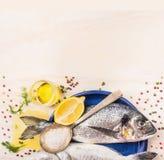 Rohe dorado Fische mit Gewürzen, Zitrone, Öl und Salz in der blauen Platte auf weißem hölzernem Hintergrund Lizenzfreie Stockbilder