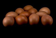 Rohe Eier auf schwarzem Hintergrund Stockbilder