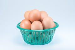 Rohe Eier im grünen Korb auf weißem Hintergrund Lizenzfreie Stockbilder