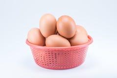 Rohe Eier im roten Korb auf weißem Hintergrund Stockbild