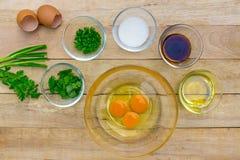 Rohe Eier und Bestandteile auf hölzernem Hintergrund Stockfotografie