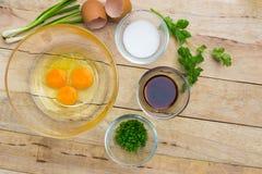 Rohe Eier und Bestandteile auf hölzernem Hintergrund Lizenzfreie Stockfotografie