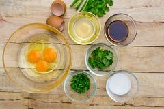 Rohe Eier und Bestandteile auf hölzernem Hintergrund Lizenzfreie Stockbilder