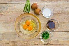 Rohe Eier und Bestandteile auf hölzernem Hintergrund Stockbilder