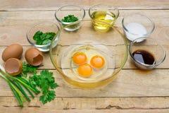 Rohe Eier und Bestandteile auf hölzernem Hintergrund Lizenzfreies Stockfoto