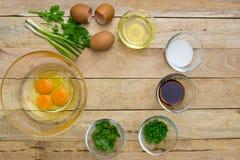 Rohe Eier und Bestandteile auf hölzernem Hintergrund Lizenzfreie Stockfotos
