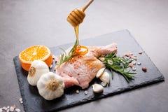 Rohe Entenbeine mit Rosmarinhonig salzen Knoblauchorange und -pfeffer stockbild