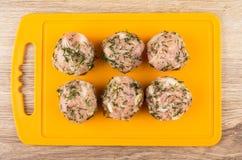 Rohe Fleischklöschen mit Dill auf orange Schneidebrett auf Tabelle Stockfoto