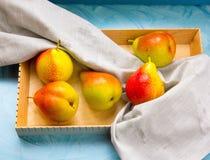 Rohe frische Birnen am hölzernen Schreibtisch am hellen Weinlesehintergrund lizenzfreies stockbild