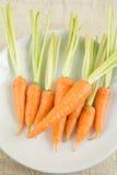 Rohe frische Karotten auf weißer Platte Stockbild