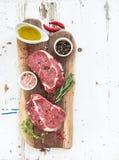 Rohe Frischfleisch Ribeye-Steakmittelrippe vom rind und -gewürze auf Schneidebrett über weißem hölzernem Hintergrund Stockfotos