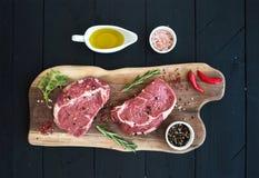 Rohe Frischfleisch Ribeye-Steakmittelrippe vom rind und -gewürze auf Schneidebrett Stockbild