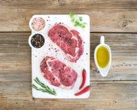 Rohe Frischfleisch Ribeye-Steakmittelrippe vom rind und -gewürze auf weißem Schneidebrett über Schmutzhintergrund Stockfoto