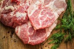 Rohe Frischfleisch-Scheiben auf hölzernem hackendem Brett Stockfotos
