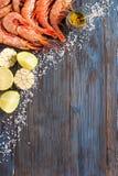 Rohe Garnele, Knoblauch, Kalk, Curry und Seesalz auf einem dunklen hölzernen Hintergrund Lizenzfreies Stockbild
