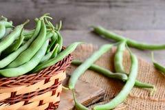 Rohe grüne Bohnen in einem braunen Korb und auf einem Leinwandgewebe Frische junge Bohnenhülsen Alter hölzerner Hintergrund Lizenzfreies Stockbild