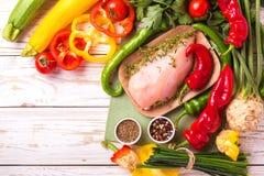 Rohe Hähnchenbrustfilets mit Gemüsebestandteilen in der Wanne Stockbilder
