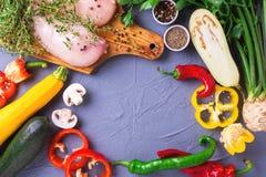Rohe Hähnchenbrustfilets mit verschiedenen Gemüsebestandteilen Stockbild