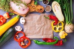 Rohe Hähnchenbrustfilets mit verschiedenen Gemüsebestandteilen Stockfoto