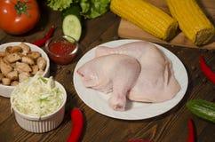 Rohe Hühnerbeine auf weißer Platte auf hölzernem Hintergrund lizenzfreies stockfoto