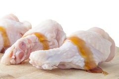 Rohe Hühnerbeine mit Auster sauce auf weißem Hintergrund Stockfotografie