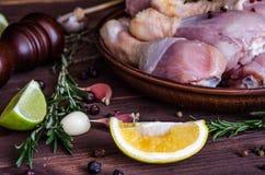 Rohe Hühnerbeine, Trommelstöcke auf der Platte, Fleisch mit Gewürzen für das Kochen lizenzfreies stockfoto
