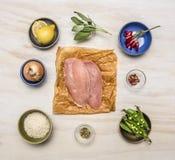 Rohe Hühnerbrust mit Zitrone, Kräuter, Pfeffer, Erbsen, Reis, Zwiebeln, Draufsichtabschluß des Hintergrundes des Senfes hölzerner Stockfoto